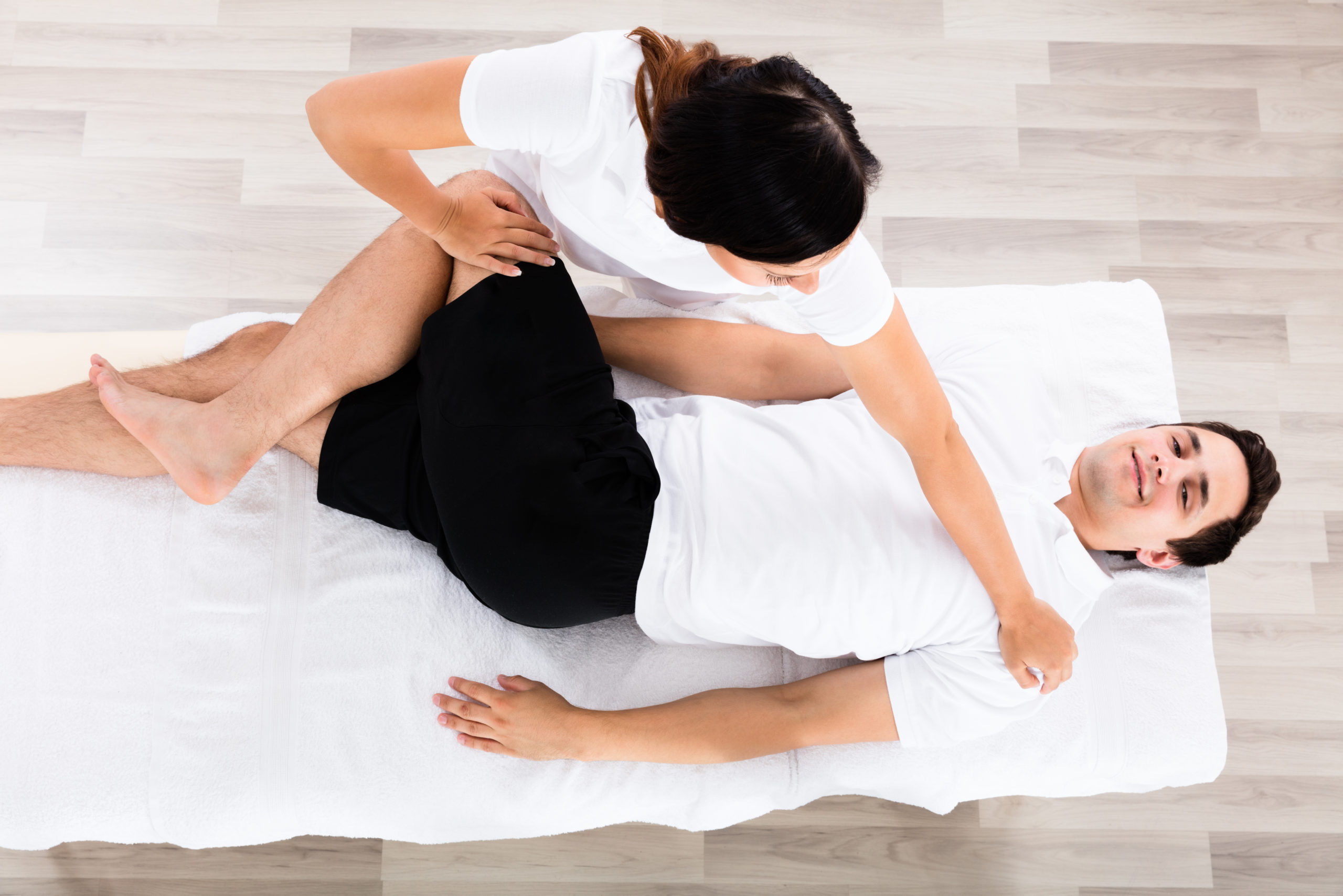 High Angle View Of A Young Female Therapist Massaging Relaxed Man's Leg